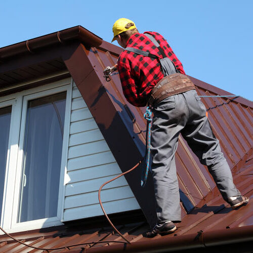 A Roofer Paints a Metal Roof.