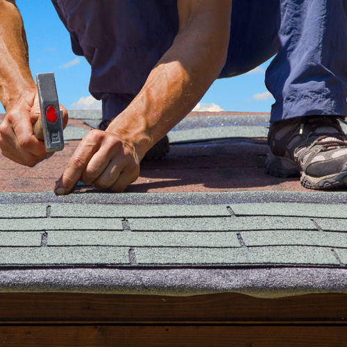 A Roofer Repairs a Damaged Roof.