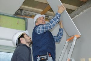 Two contractors install drywall roofing after making roof repairs