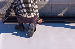 A Man Applying a PVC Membrane To a Roof