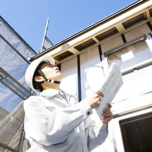 Man Holding Papers Conducting Roof Inspection
